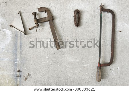old hacksaw and clamp  hanging on garage wall - stock photo