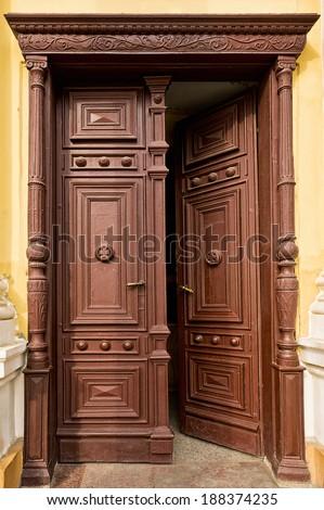 Old  half-opened wooden door in church - stock photo