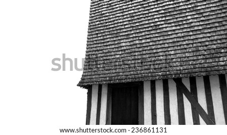 Old half timbered house house wall with traditional wooden tiled roof. Aged photo. Black and white. - stock photo