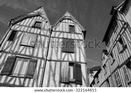Old half timbered houses in medieval town of Auxerre (Burgundy, France).  Aged photo. Black and white. - stock photo