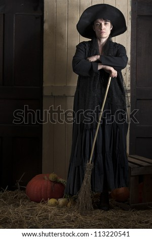 old halloween witch with broom and pumpkin in a barn
