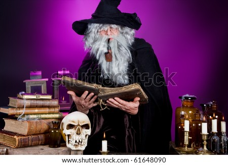 Old halloween wizard reading a spell book in his kitchen - stock photo