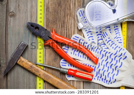 Old hammer, pliers, screwdriver, tape measure, gloves and safety glasses on old textured boards bench. still life with working tools - stock photo