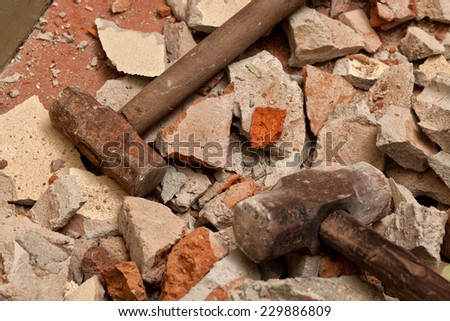 Old hammers on broken brick wall - stock photo