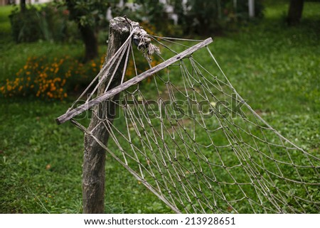 old hammock hanging in the garden - stock photo