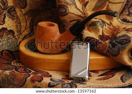 old hand carved tobacco pipe and wood and metallic ashtray and lighter
