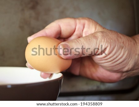 Old Hand Cracking and pouring an Egg into a Bowl.