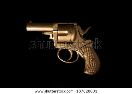 Old hand gun revolver with an aged golden patina displayed sideways on a dark background with copyspace - stock photo