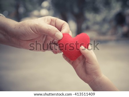 old hand of the elderly and a young hand of a baby holding a red heart together - stock photo