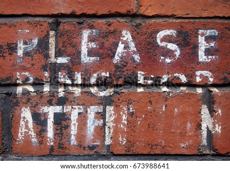 old hand painted notice saying please ring for attention on brick wall