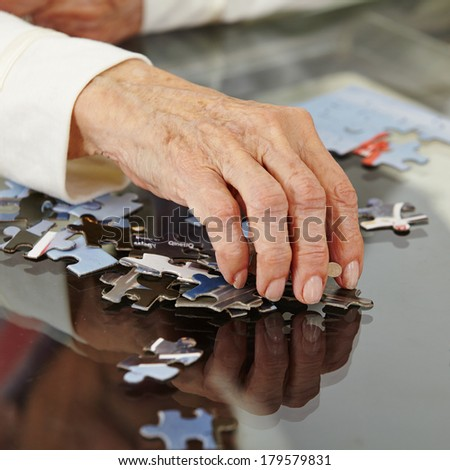 Old hand with wrinkles reaching for a jigsaw puzzle piece - stock photo