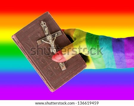 Old hand (woman) holding a very old bible, isolated on white, rainbow flag - stock photo