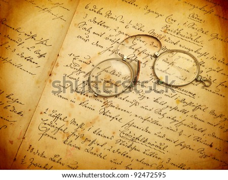 old, hand-written cook book with monocle - stock photo