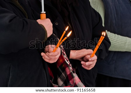 old hands and candle lights, close-up hands, romaninas peasants celebrating the dead ones at the church, traditional feast in a rainy day