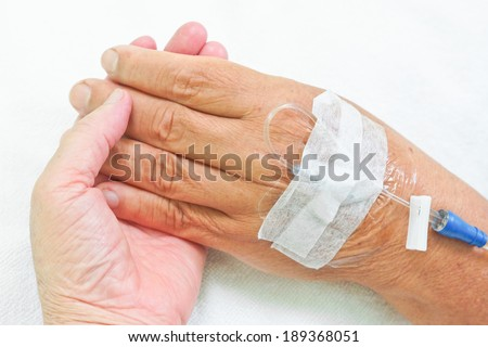 old hands holding each other with IV solution in a patient's hand