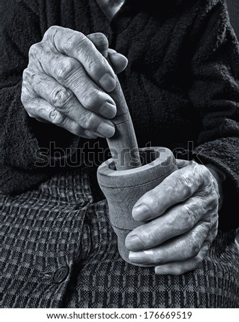 Old hands holding wooden mortar. Black and white image. - stock photo