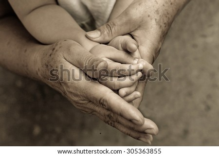 old hands holding young hand of a baby with love - stock photo