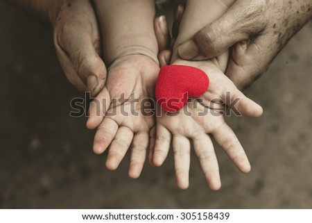 old hands holding young hand of a baby with red heart - stock photo