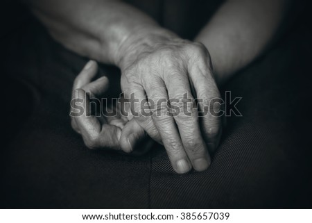 Old hands of elderly man on his knees