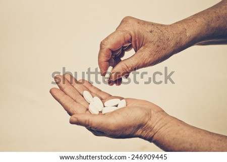 Old hands of the elderly hold drug pills - stock photo