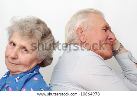 old happy couple sitting back to back