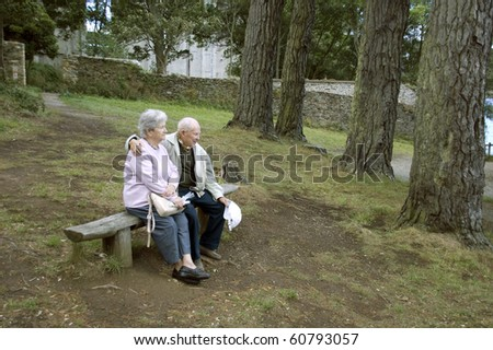 Old happy senior couple sitting on bench