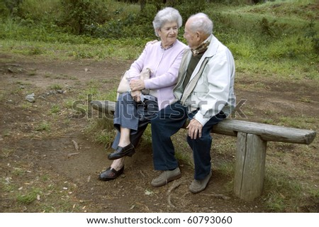 Old happy senior couple sitting on bench - stock photo
