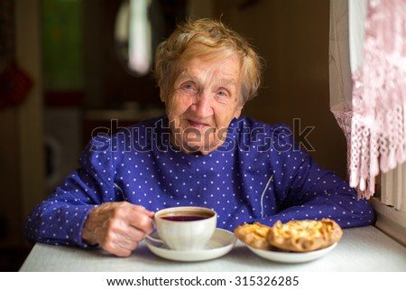 Old happy woman drinking tea in her kitchen.