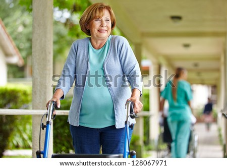 Old happy woman with walker on a stroll in the park of a nursing home - stock photo