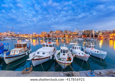 Old harbour of Heraklion with fishing boats and marina during twilight blue hour, Crete, Greece. Boats blurred motion on the foreground. - stock photo