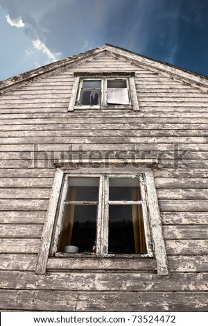 Old haunted house with two dark windows - stock photo