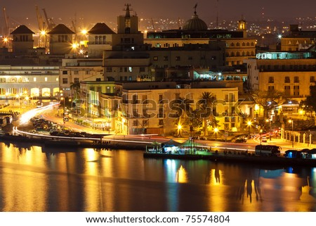 Old Havana and parts of the bay illuminated at night with reflections on the water - stock photo