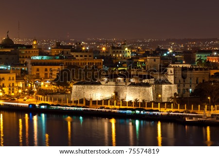 Old Havana including the walls of the fortress of La Fuerza , its surrounding historical area and parts of the bay illuminated at night with reflections on the water