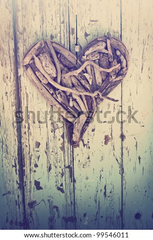 old heart made of driftwood on vintage wood wall background.
