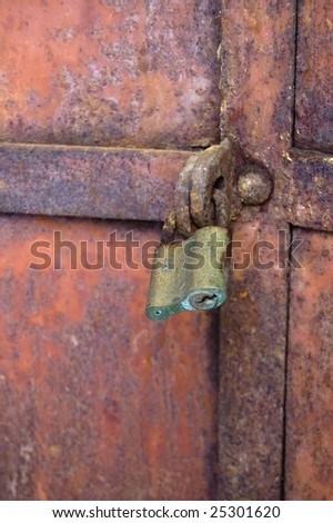 Old heavy rusty door with locker - stock photo