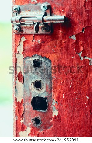 Old heck on old shabby door at day - stock photo