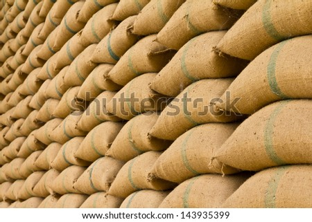 Old hemp sacks containing rice placed profoundly stacked in a row to keep up. - stock photo