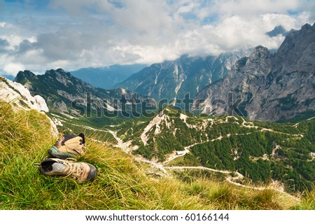 Old hiking boots on mountains background - stock photo