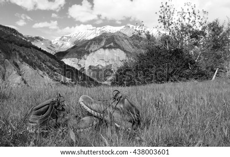 Old hiking shoes and Alpine landscape at background. Provence-Alpes-Cote d'Azur region of France. Black and white photo. - stock photo
