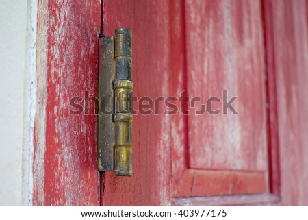 Old hinge door with red wood door blur background:Close up,select focus with shallow depth of field:ideal use for background. - stock photo