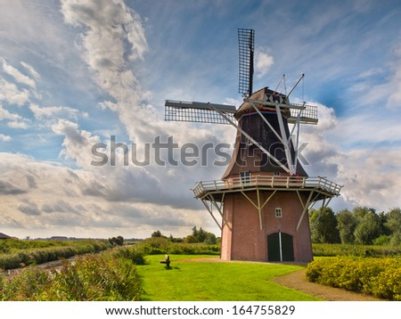 Old Historic Dutch Windmill besides a Canal in Rural Countryside - stock photo