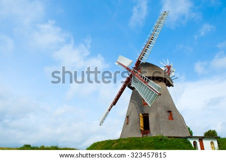 old historic windmill in front of blue sky - stock photo