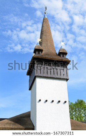 Old historical spire or bell tower on a church against a cloudy blue sky - stock photo