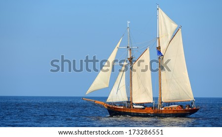 old historical tall ship (yacht) with white sails in blue sea - stock photo