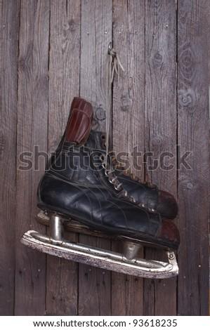old hockey skates on background of wood - stock photo
