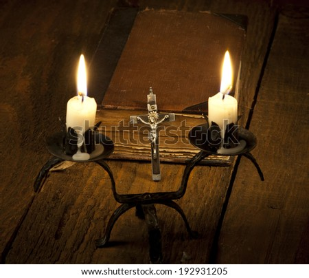 Old Holy Bible, candles and Crucifix on wooden background. - stock photo