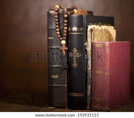 Old Holy Bibles and Wooden Rosary Beads on Wooden Background. - stock photo