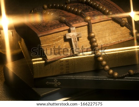 Old Holy Bibles, Rosary Beads and Candles. - stock photo