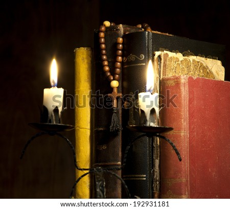 Old Holy Bibles, Wooden Rosary Beads and Candles on Wooden Background. - stock photo