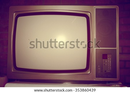 Old home television on a vintage filter on a brick wall background